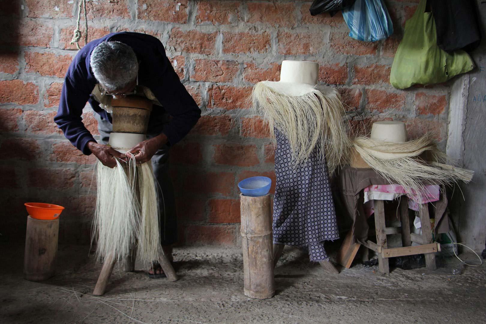 artesano trabajando un sombrero de jipi japa